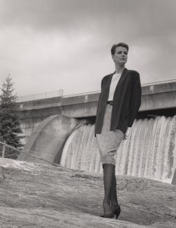 Image of a woman posing in front of a hydroelectric dam.